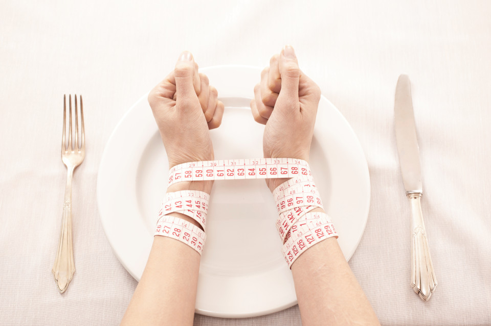 eating disorder hands on plate image