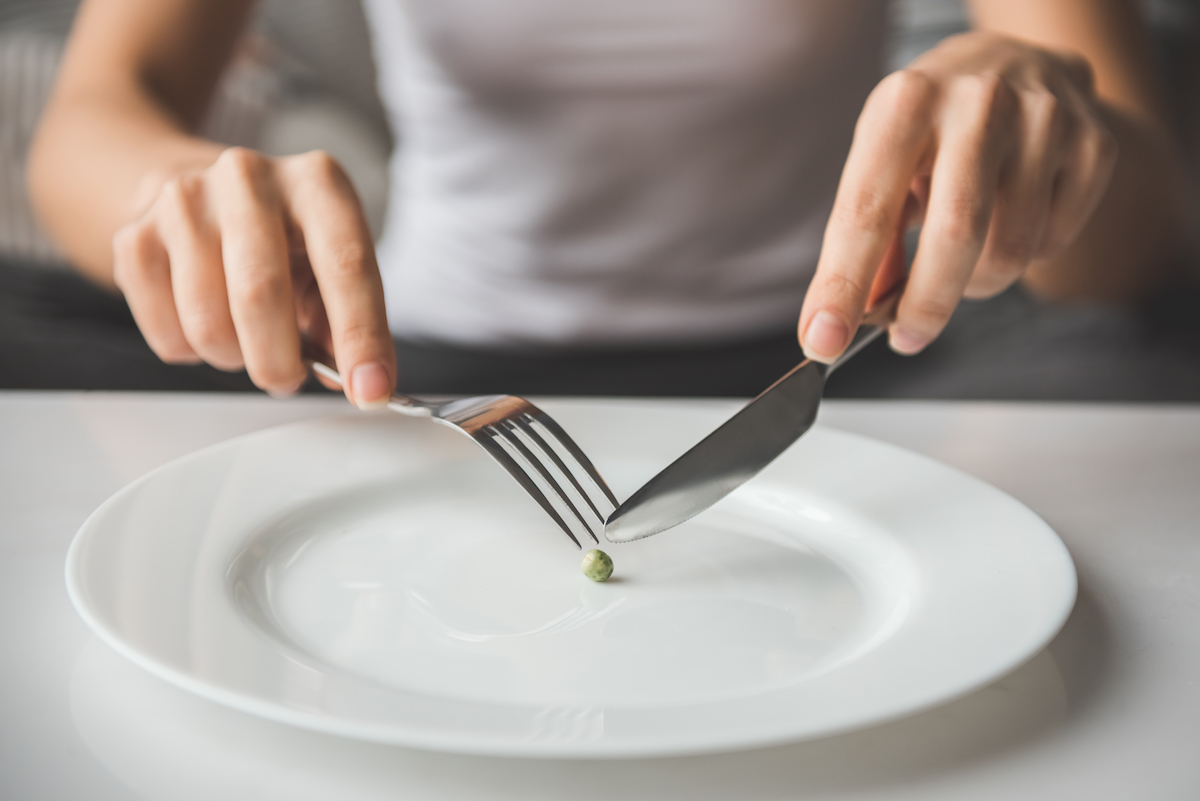 image of girl trying to put a pea on the fork